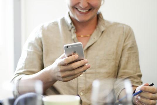 Joakim tittar på telefonen och skrattar